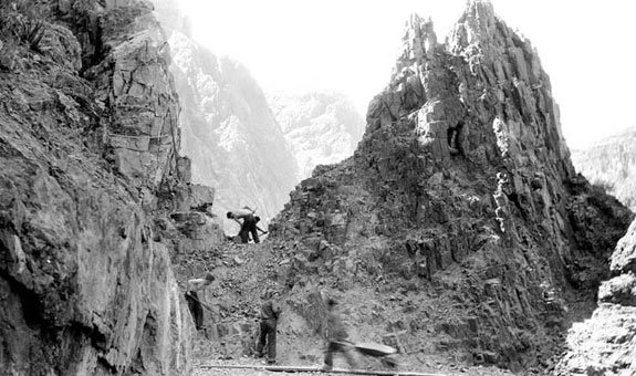 Colorado River trail construction by CCC enrollees. Men working on cut area between rock formations. Circa 1934. NPS. Grand Canyon National Park Museum Collection