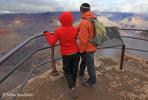 Couple looking over the storm Grand Canyon rim | Photo by Mike Buchheit