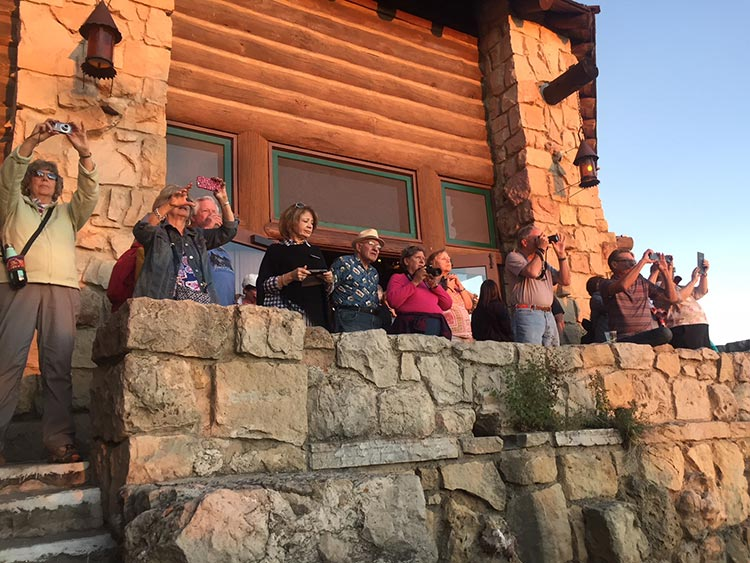 Visitors photograph the setting sun from the Grand Canyon Lodge on North Rim