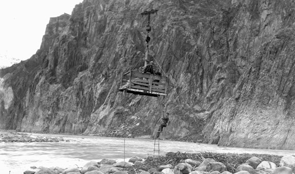 CCC Men above Colorado River in Cable Car. Men Hanging from Car with Rope Ladder